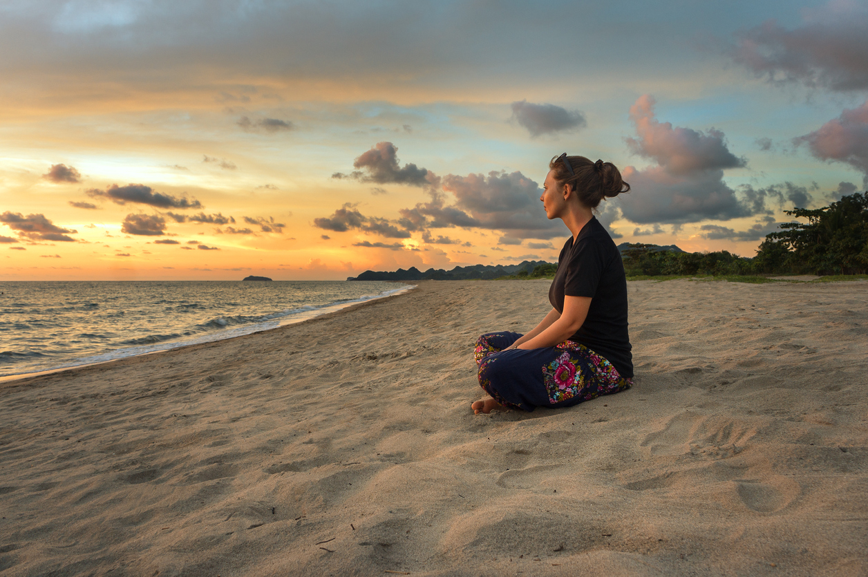 Woman relaxing on beach at sunset
